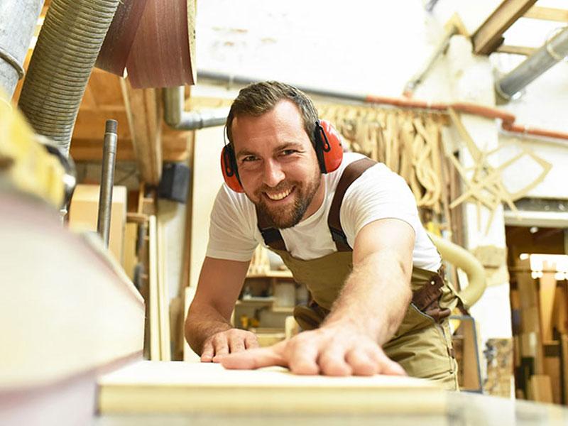 man cutting timber